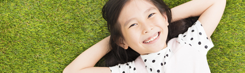 A preschool girl lies in the grass and is feeling confident and ready for Kindergarten with skills she learned through KidSquad